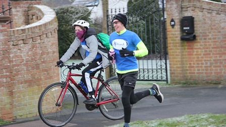 Jack Bartle running alongside his dad, Andrew, on a bicycle.
