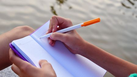 The girl keeps a secret diary. Female hand writes a letter on the lake. Writing our thoughts in a no