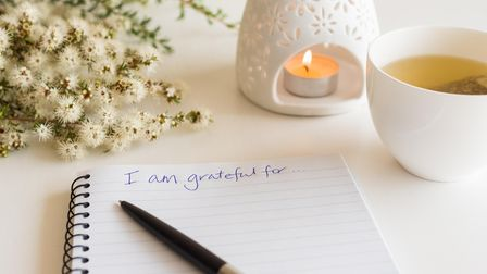 """Close up of handwritten text """"I am grateful for..."""" in foreground with notebook, pen, cup of tea, f"""
