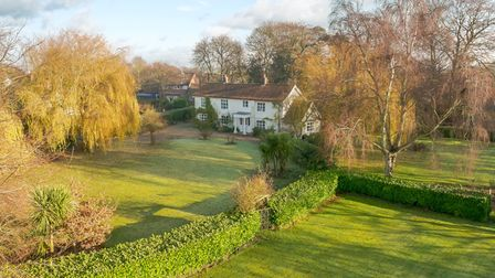 Secluded white country house surrounded by trees, lawns and hedges