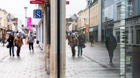 Members of the public are reflected in the window of the empty shop in Ipswich