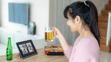 Woman on video call with her friends on a tablet, while holding a beer