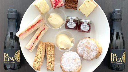 An overhead shot of an afternoon tea with sandwiches, scones, preserves and bottles of fizz