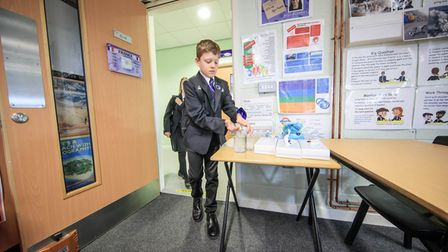 Pupils using hand sanitiser as they enter a classroom.