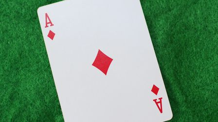 Ace of diamonds single playing card on green base background