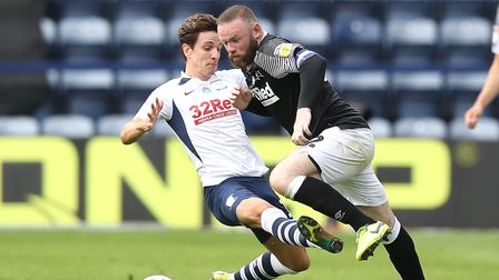 Preston North End's Josh Harrop (left) and Derby County's Wayne Rooney battle for the ball during th
