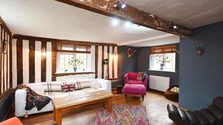 Period style living room with exposed studwork, beams and a large white sofa in the centre