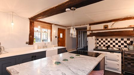 Contemporary country style kitchen with exposed beams white Aga and black and white tiles