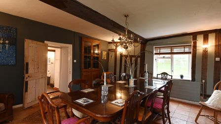 Dark coloured dining room with exposed timber beams and a large dining table in the centre