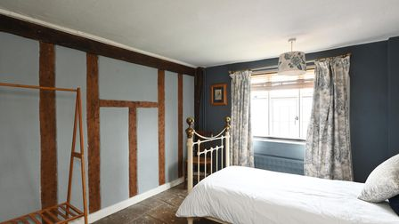 Country style bedroom with exposed beams on the wall and a stripped wooden floor