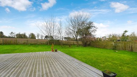 Large raised decking area set in expansive lawn with views of the horizon and over neighbouring fields