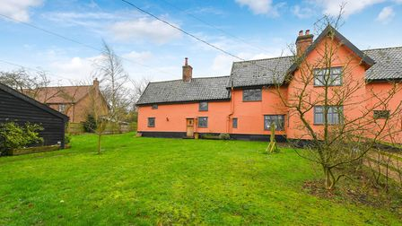 Terracotta coloured farmhouse with attached annexe sat in large lawned gardens