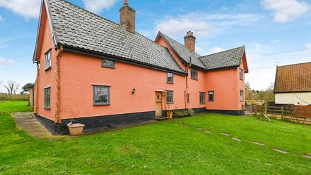 Pink terracotta coloured farmhouse with pantile roof set in large grassy gardens