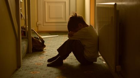 sad child with his head between his legs left alone at home. Picture: Getty Images/iStockphoto