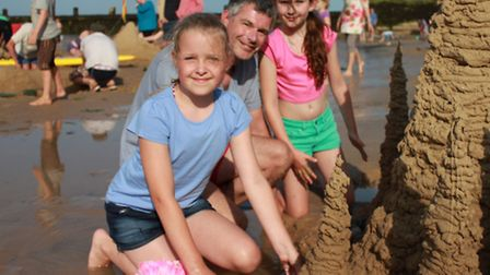 John Brine, his ten-year-old daughter Catherine (right) and her friend Mica, 10, add the finishing t