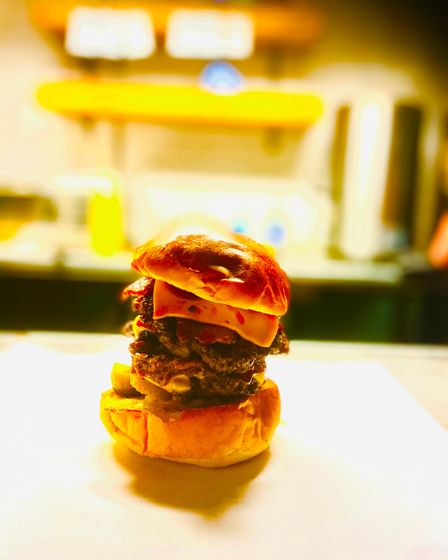 A picture of a Wagyu burger on a countertop in a food truck