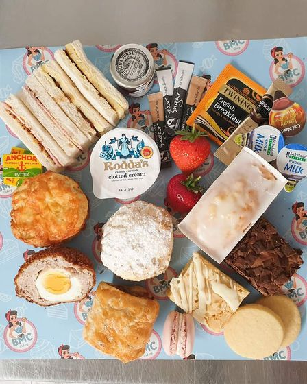 An overhead shot of an afternoon tea platter, featuring cakes, sandwiches, Scotch eggs, teas and jams
