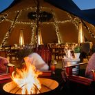 The Weeping Willow pub's winter garden. It features a tent filled with fairy lights, fire pit and chairs