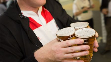 A man holding three pints of beer at the Great British Beer Festival (GBBF) in Olympia London, Keni