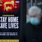 A member of the public walks passed a coronavirus related advert on a bus stop.