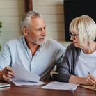 Older grey-haired couple signing and filling in documents together at home