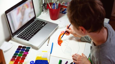 Child draws with watercolors using instructions on laptop.