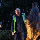 David Irvine, co-ordinator of Bury in Bloom next to the wolf sculpture on the roundabout in Bury St