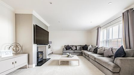 Contemporary living room with large grey sofa and widescreen TV mounted on the wall