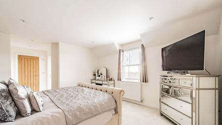 Large bedroom with double bed and TV on top of a silver chest of drawers