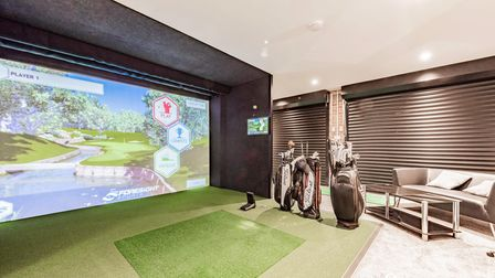 Large golf simulator with golf clubs and caddies inside a private double garage