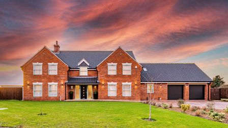 Large modern brick-built house with sleeping front lawn and gorgeous sunset sky behind it