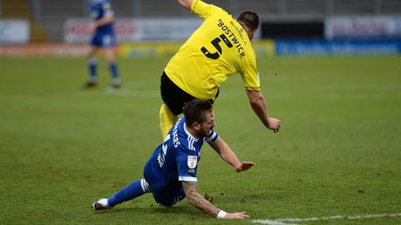 Luke Chambers slides underneath Michael Bostwick at Burton Albion and gets booked for it. Picture Pa