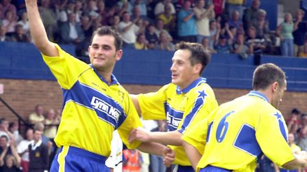Adie Hayes waves in triumph as he is congratulated by Lee Hudson after scoring from the penalty sp