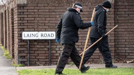 Police officers search the area near Laing Road after a woman was found dead on Sunday morning.