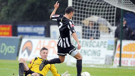 Action from Dereham Town v Soham Town at Aldiss Park - Dereham's Craig Bussens rounds the keeper to