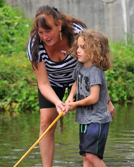 Messing about in the river just like when she was a kid Pam Rust helping grandson Deacon catch fish