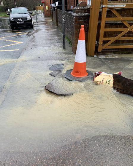 traffic cone marking pavement damage and flood water