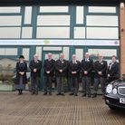 Funeral directors team standing outside with hearse