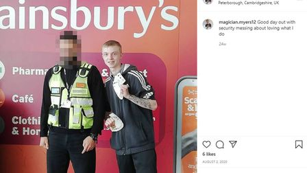 Myers poses with a Sainsbury's security guard.