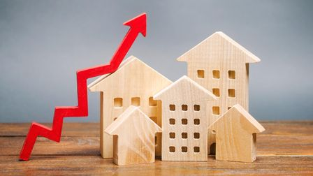 Miniature wooden houses and red arrow up. The concept of increasing the cost of housing. High demand