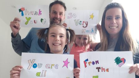 The Evans family holding up messages of thanks to teachers
