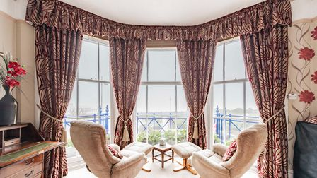 Large bay window overlooking the seaside with frilled curtains and two chairs sat side by side with a coffee table in the middle