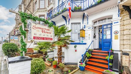 Photograph of the front of Somerton House guesthouse with a small patio garden with pots outside and a bright blue door with steps leading up