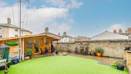 Photograph of a small back garden with artificial grass laid, a small stone patio and a log cabin