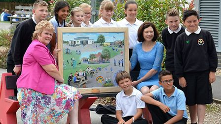 Artist Heath Rosselli presents Wendy Garrad with a painting to mark her retirement as headteacher at
