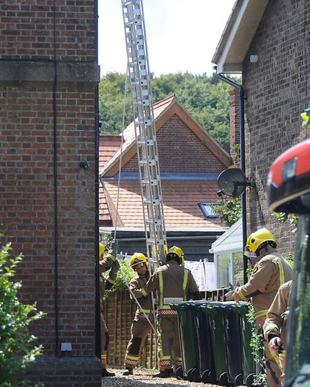 Cat stuck on a roof in Park Road, Cromer. Firefighters prepare to rescue the cat.Picture: ANTONY KEL