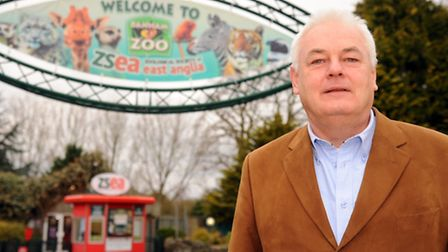 Martin Goymour of Banham Zoo stands with the signs announcing control of the zoo has changed to the