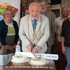 William Armstrong, sheriff of Norwich, cuts the cake to celebrate Norwich Credit Union's 25th annive