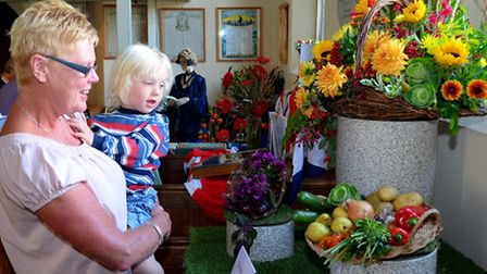Visitors admire the displays at the flower festival in Somerleyton church.
