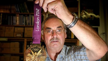 Auctioneer David James holding the London 2012 Olympic gold medal which was donated to a charity auc